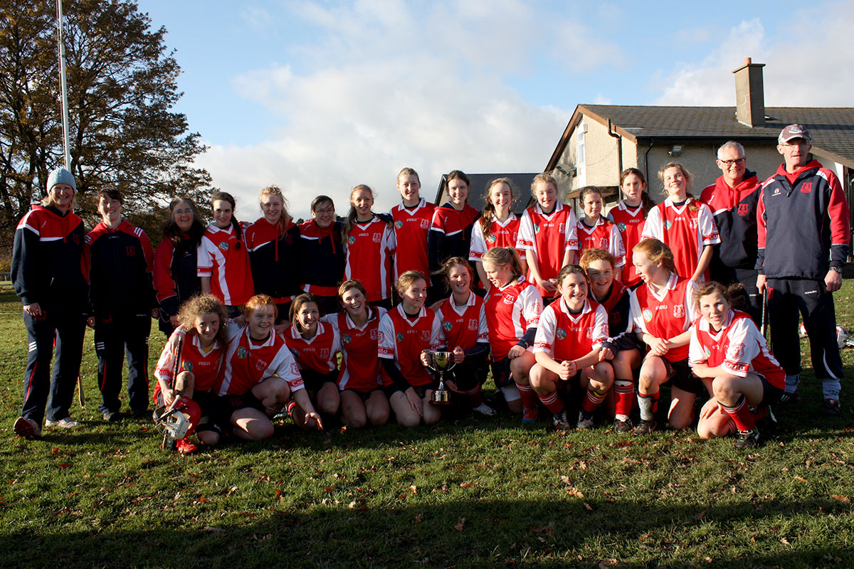U14 Cuala Camogie Team and mentors with Championship cup